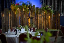 Our Rustic stage and backdrop with pendant lamps, floral arrangement by Wildflower